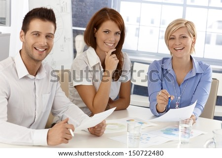 Happy businessteam at meeting, working with documents, laughing, looking at camera. - stock photo