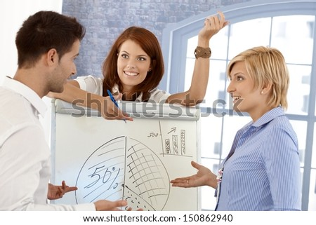 Happy businessteam discussing diagram on whiteboard in meeting room, smiling. - stock photo