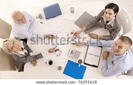 Happy businessteam working together, smiling, pointing at document, overhead view.?