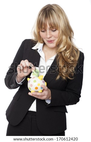 Happy businesswoman adding to her savings inserting a 100 euro banknote into her cute yellow polka dot piggy bank with a smile of satisfaction, isolated on white - stock photo