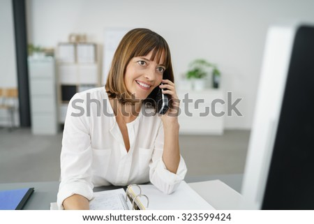 Happy Businesswoman at her Table, Talking to Someone Using her Mobile Phone - stock photo