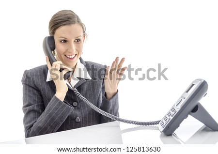 Happy businesswoman at office desk talking on the phone. Isolated on a white background. - stock photo
