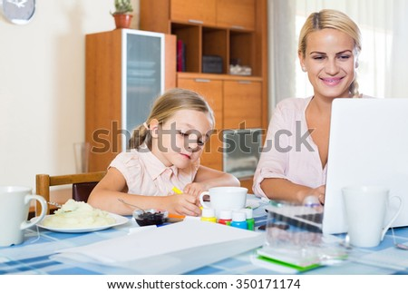 happy businesswoman browsing internet at home, daughter drawing  in pencil. focus on girl - stock photo