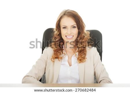 Happy businesswoman by a desk. - stock photo