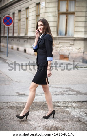 Happy businesswoman calling on street, real estate - stock photo
