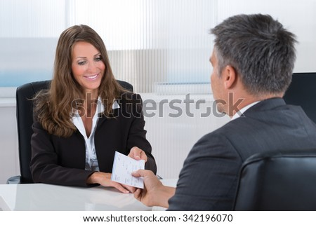 Happy Businesswoman Giving Cheque To Businessman In Office - stock photo