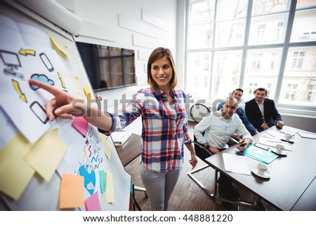 Happy businesswoman giving presentation as colleagues look at her during meeting in creative office - stock photo