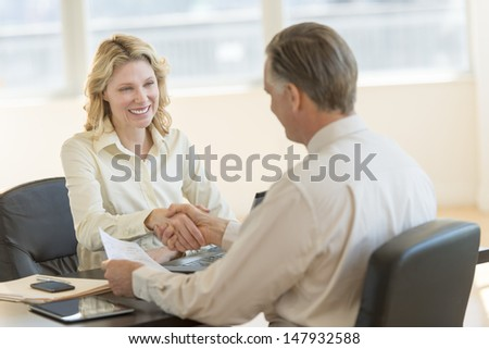 Happy businesswoman greeting male colleague at desk in office - stock photo