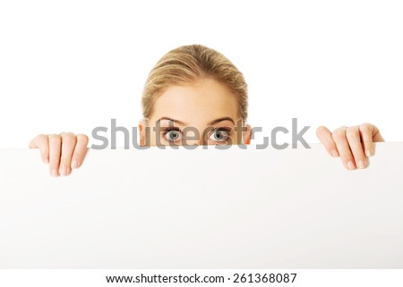 Happy businesswoman hiding behind an empty billboard
