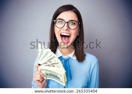 Happy businesswoman holding bill of dollars and screaming over gray background. Wearing in blue shirt and glasses. Looking at camera - stock photo