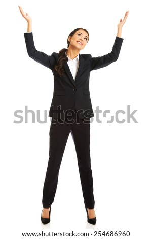Happy businesswoman holding copyspace high. - stock photo