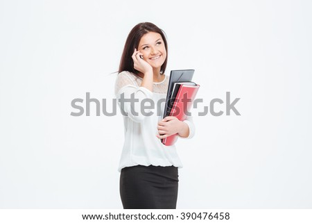 Happy businesswoman holding folders and talking on the phone isolated on a white background - stock photo
