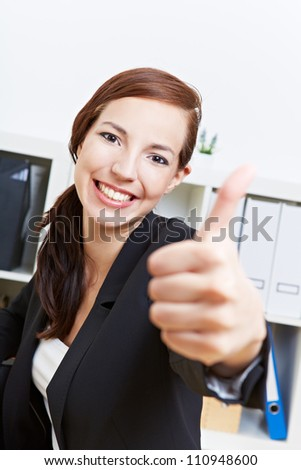 Happy businesswoman holding her thumbs up in the office - stock photo