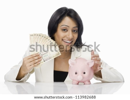 Happy businesswoman holding Indian paper currency and piggy bank - stock photo