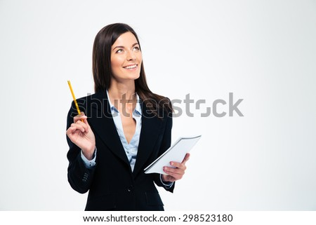 Happy businesswoman holding pencil with notebook and looking up isolated on a white background - stock photo