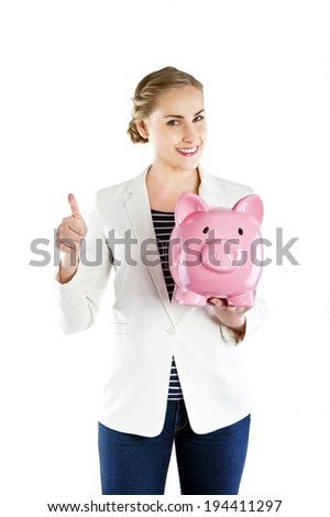 Happy businesswoman holding piggy bank against white background with thump up