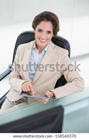 Happy businesswoman holding tablet in bright office