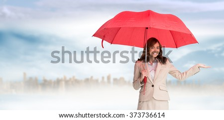 Happy businesswoman holding umbrella against large city on the horizon - stock photo