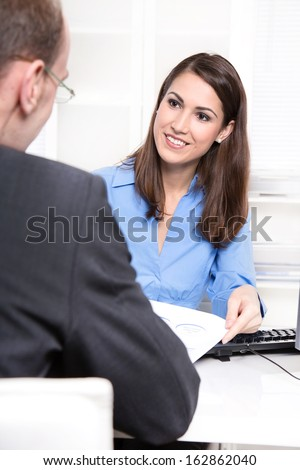 Happy businesswoman in a blue blouse in interview or meeting with a man also as consultant for a insurance.  - stock photo
