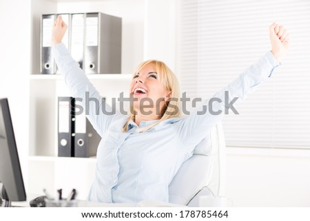 Happy Businesswoman in the office with raised arms.