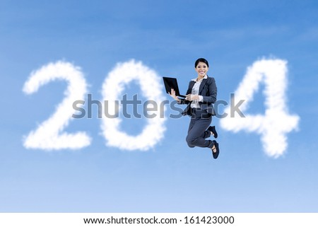 Happy businesswoman jumping with a laptop on shaped clouds of new year 2014 - stock photo