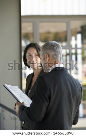Happy businesswoman listening to male colleague reading documents in office - stock photo