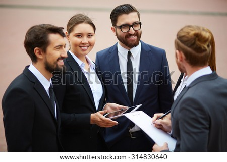 Happy businesswoman looking at camera during talk with colleagues - stock photo