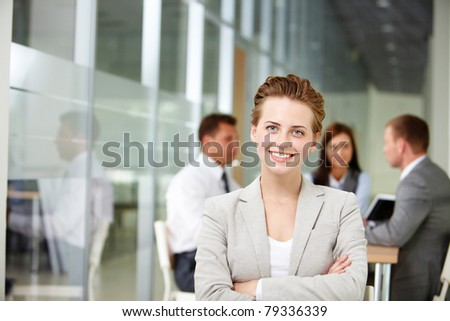 Happy businesswoman looking at camera on backround of working partners - stock photo