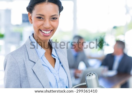 Happy businesswoman looking at camera with her colleagues behind her in office - stock photo