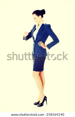 Happy businesswoman looking at her watch on wrist. - stock photo
