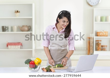 Happy businesswoman looking at laptop while preparing food in kitchen