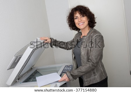 Happy businesswoman making copies on the photocopy machine at the office - stock photo