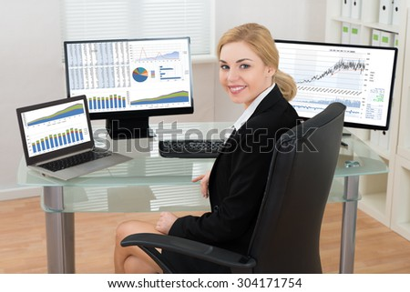 Happy Businesswoman On Office Chair With Computers Display Showing Graphs At Desk - stock photo