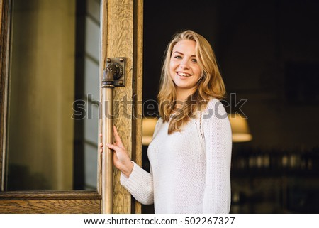 Happy businesswoman open the doors of her Coffee Shop. Service Restaurant Concept