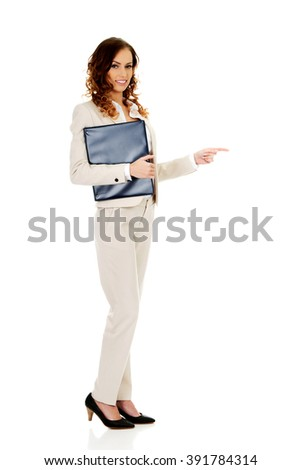 Happy businesswoman pointing with clipboard.