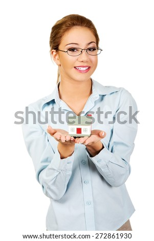 Happy businesswoman presenting a house model. - stock photo