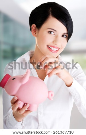 Happy businesswoman putting an euro coin into piggy bank - stock photo