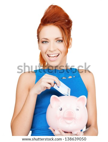 happy businesswoman putting cash money into piggy bank