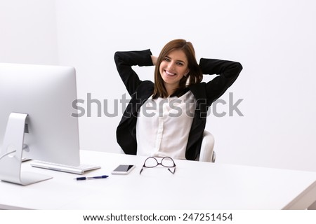 Happy businesswoman resting while sitting at the table in office