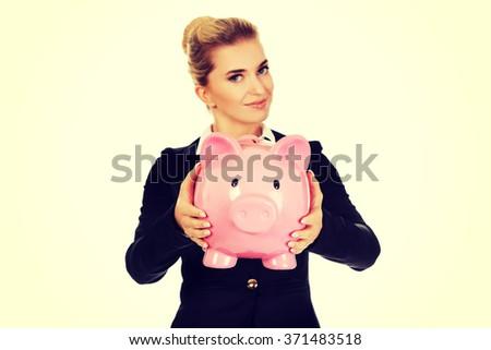 Happy businesswoman saving money in piggybank - stock photo