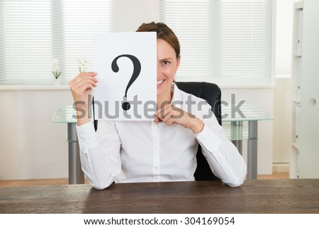 Happy Businesswoman Showing Question Mark On Paper At Desk