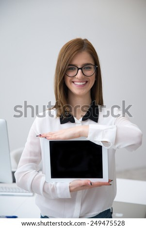 Happy businesswoman showing tablet computer screen - stock photo