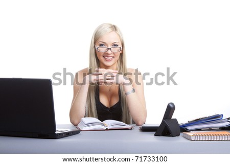 Happy businesswoman sitting at office desk, smiling. Isolated on white background.