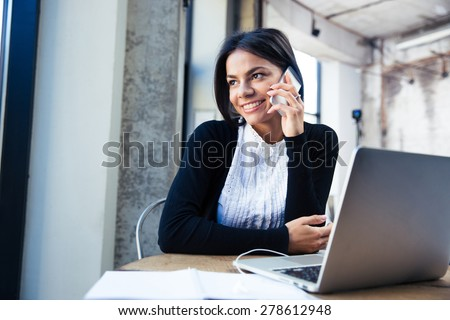 Happy businesswoman sitting at the table and talking on the phone in cafe. Looking away - stock photo