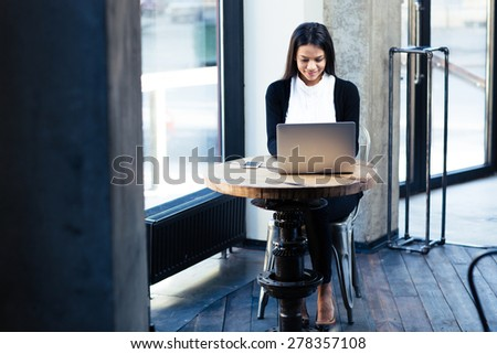 Happy businesswoman sitting at the table and using laptop in cafe - stock photo