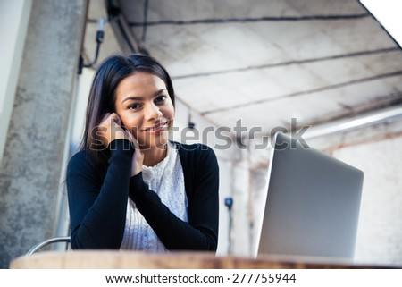 Happy businesswoman sitting at the table with laptop in cafe and looking at camera