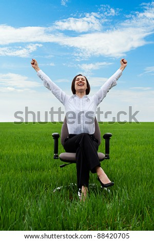 happy businesswoman sitting on chair over green meadow