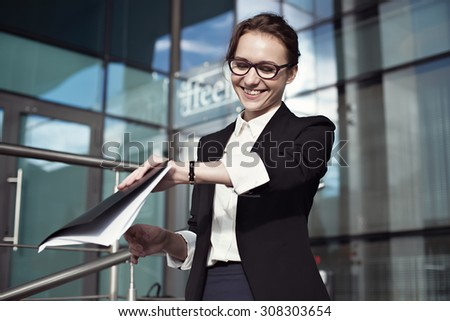 Happy businesswoman smilling and checking watch. Concept photo with young success businesswoman, her documents and time keeper on background of office. - stock photo
