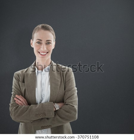 Happy businesswoman standing arms crossed against grey background - stock photo