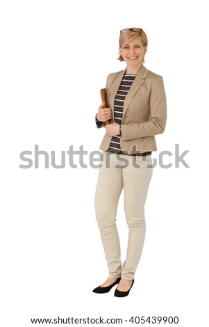 Happy businesswoman standing over white background, smiling, looking at camera. - stock photo